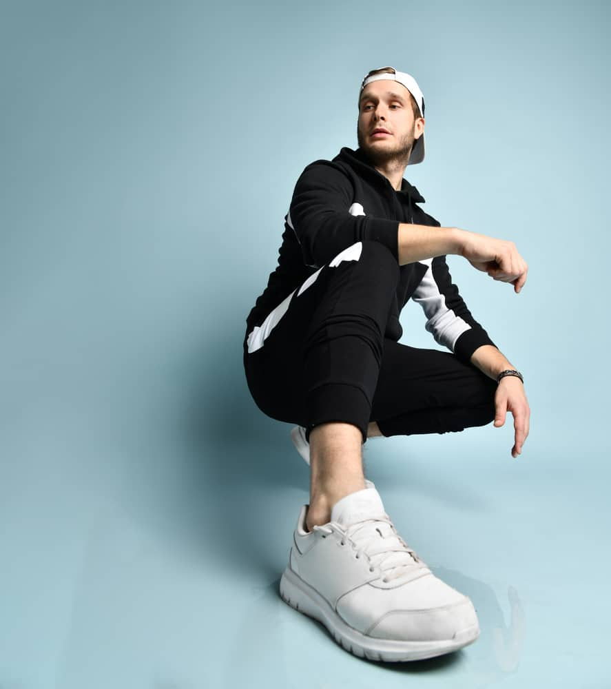 Man wearing black tracksuit, white sneakers, and a matching cap.