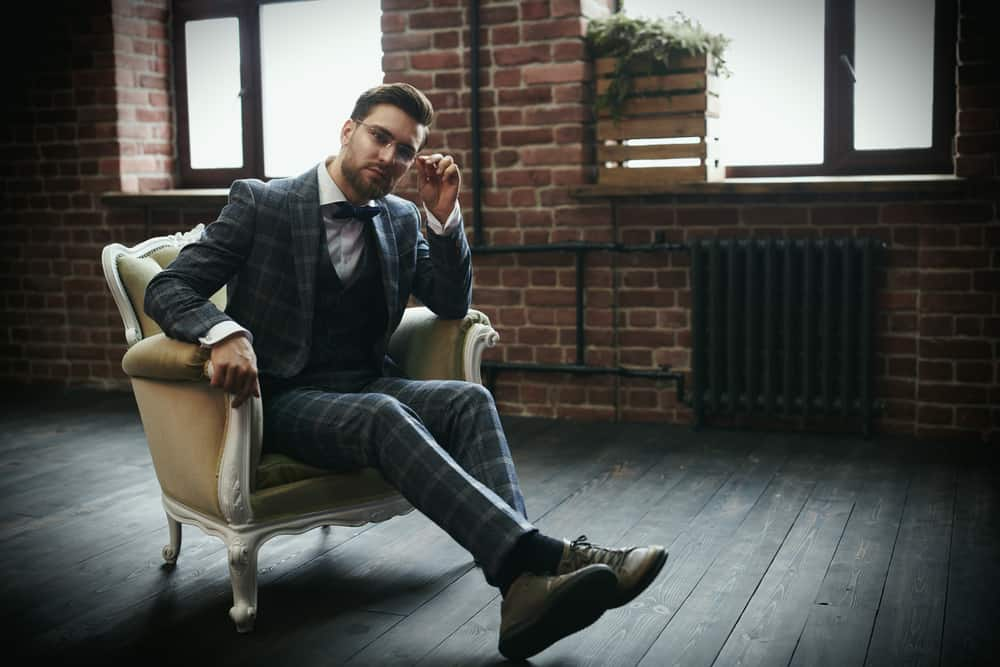 Man in classic suit and glasses sitting on a vintage chair.