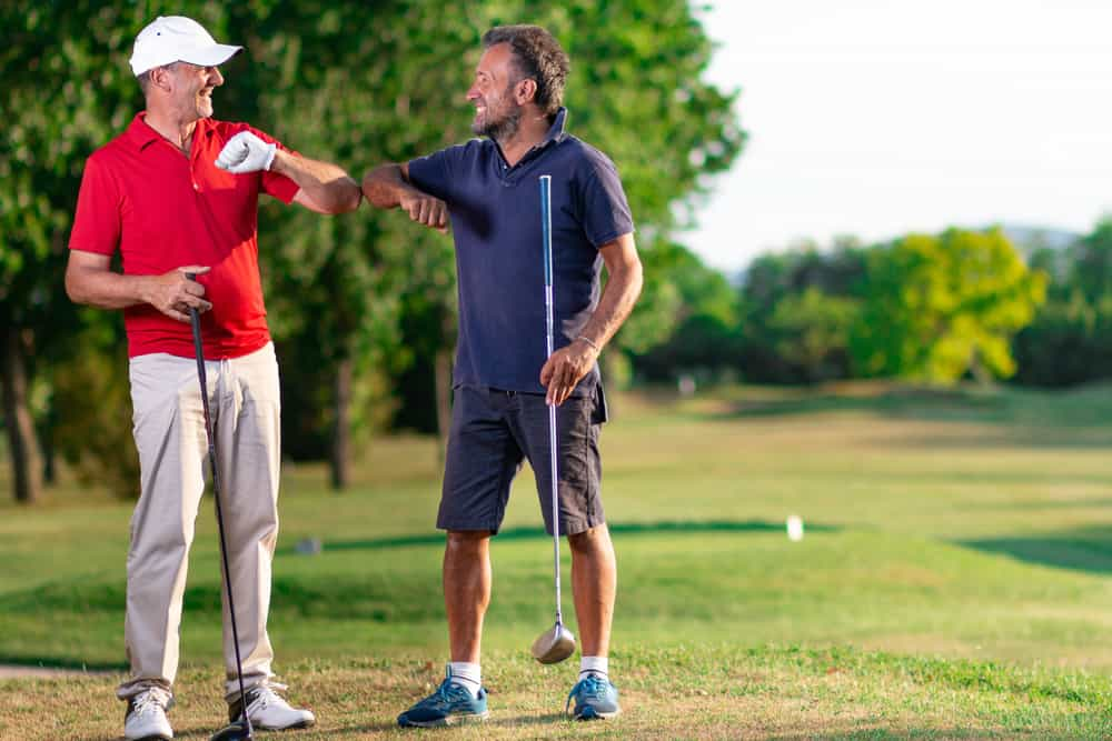 Two golf friends greet each other by touching their elbows.