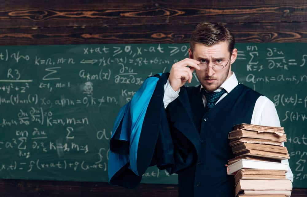 Professor holding a pile of books as he looks over his glasses.