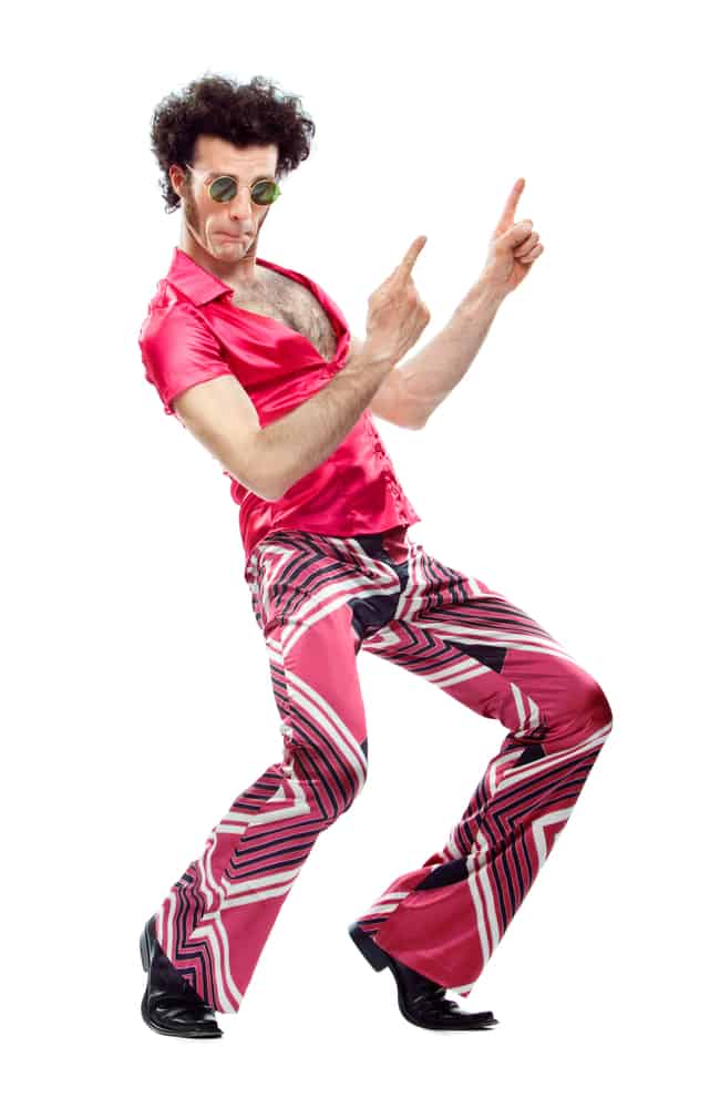 Man in a disco outfit with pink shirt and matching wide pants.