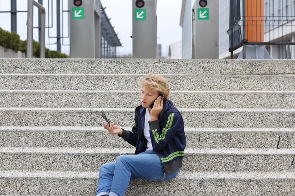 Teenage boy sitting on a city street with his phone and glasses.