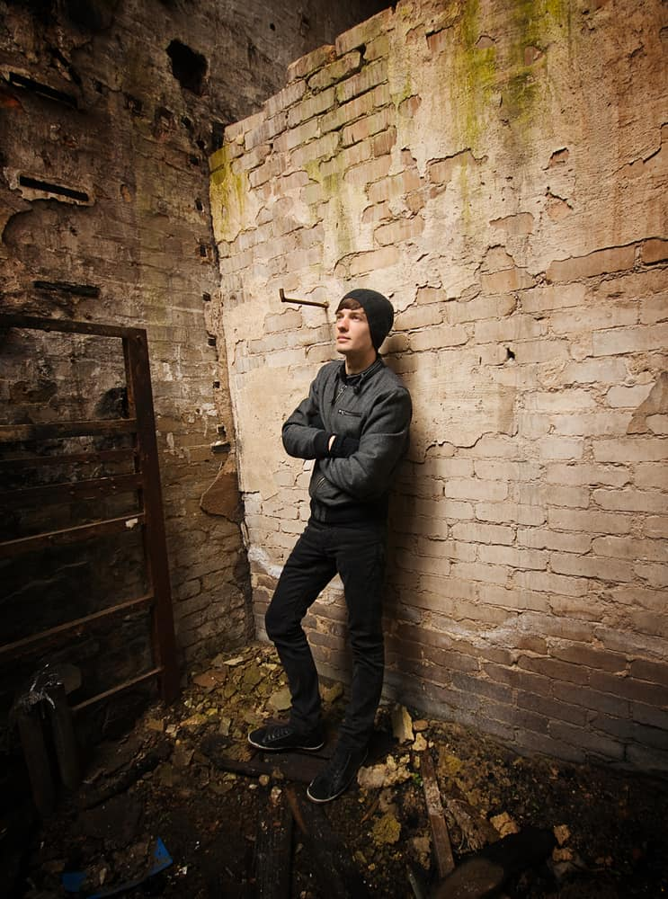 A teen boy with beanie, black jacket, and pants standing in an abandoned area.