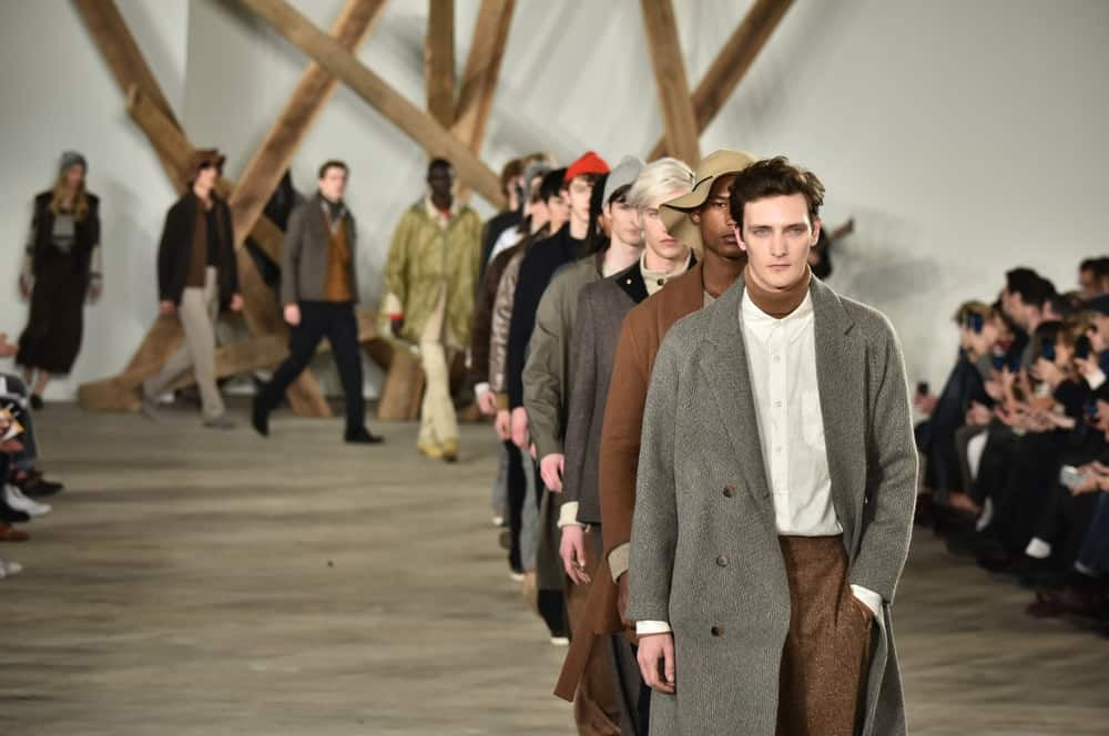 Male models in trench coats walk the runway.