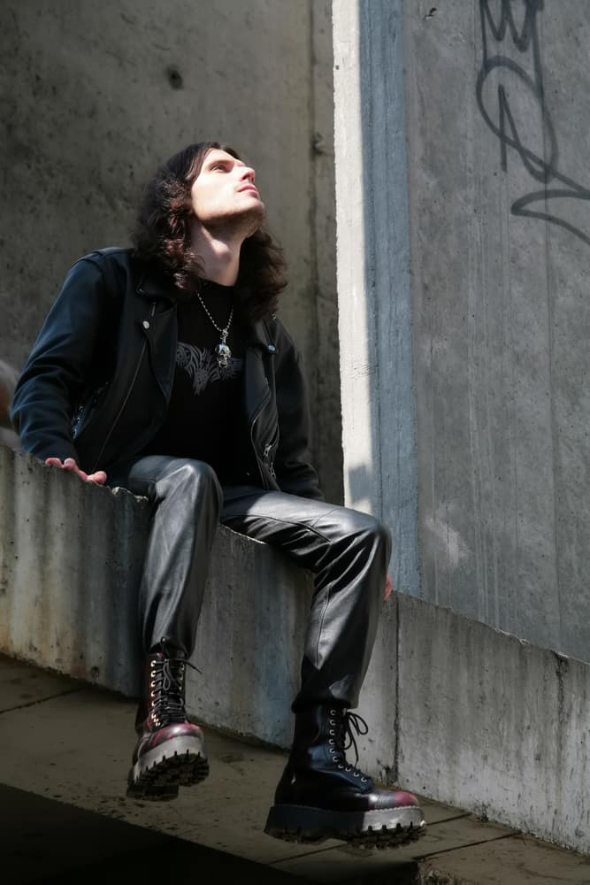 Man in a goth outfit sitting on a concrete surface.