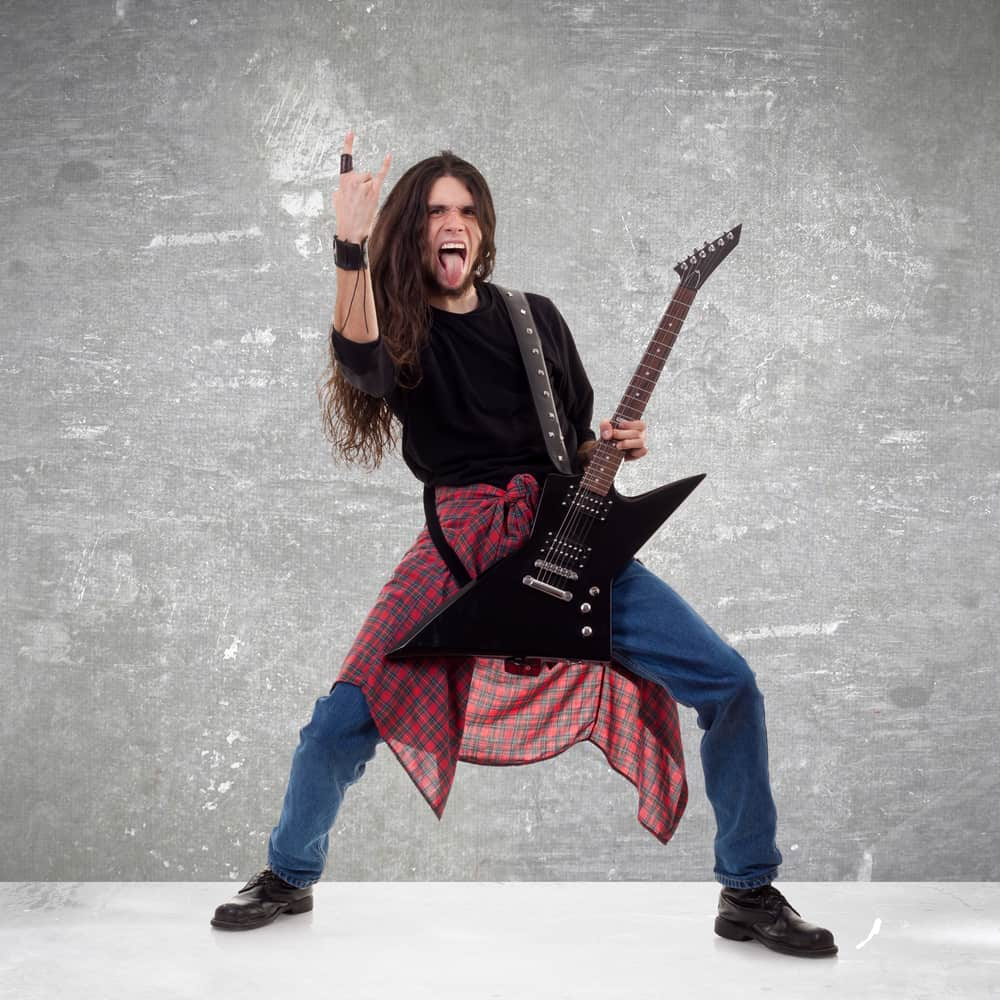 Long haired guitarist making a rock hand gesture.