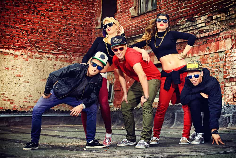 Group of young people in hip hop outfit posing together.