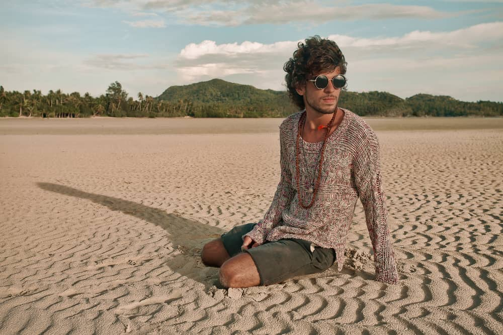A hippie in sunglasses sitting on the beach sand.
