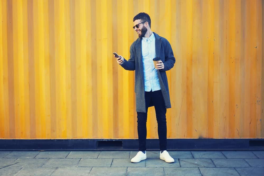 Bearded hipster holding a cup of coffee while using his phone on the other hand.