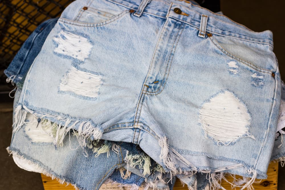 This is a close look at a stack of distressed and ripped jean shorts.