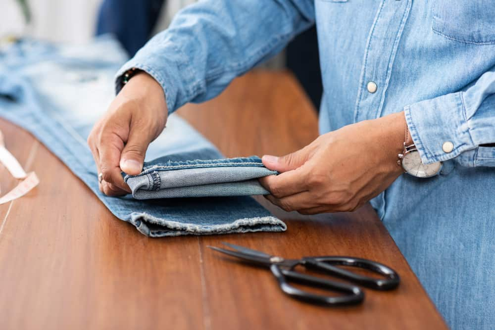 This is a close look at a tailor working on the hem of a pair of jeans.