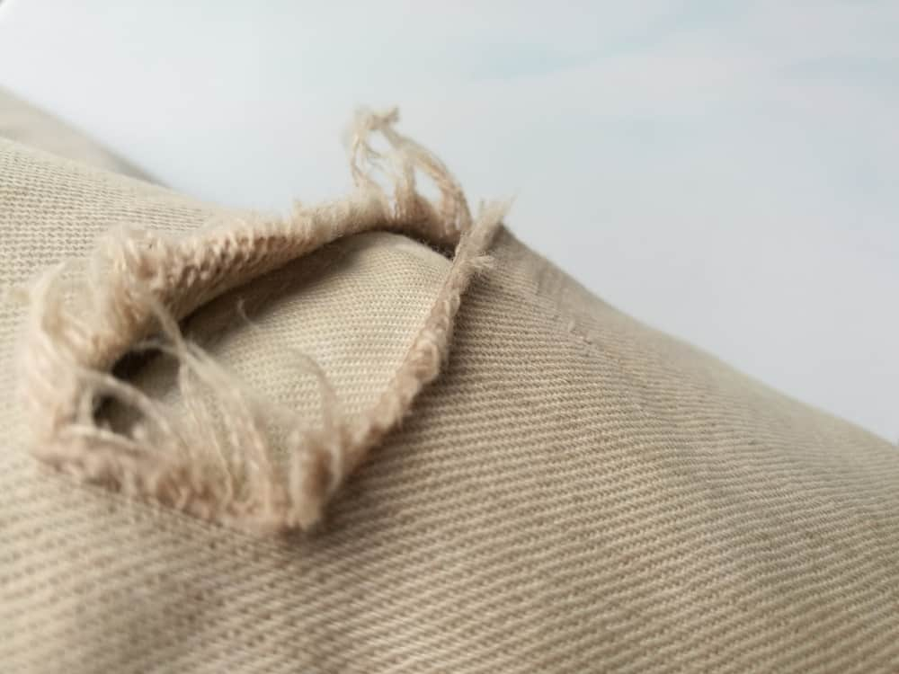 This is a close look at a pair of jeans with a frayed tear.
