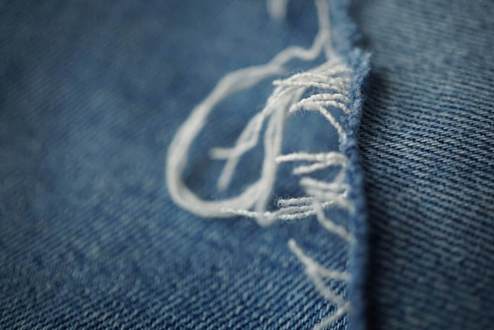 This is a close look at the frayed tear of a pair of blue jeans.