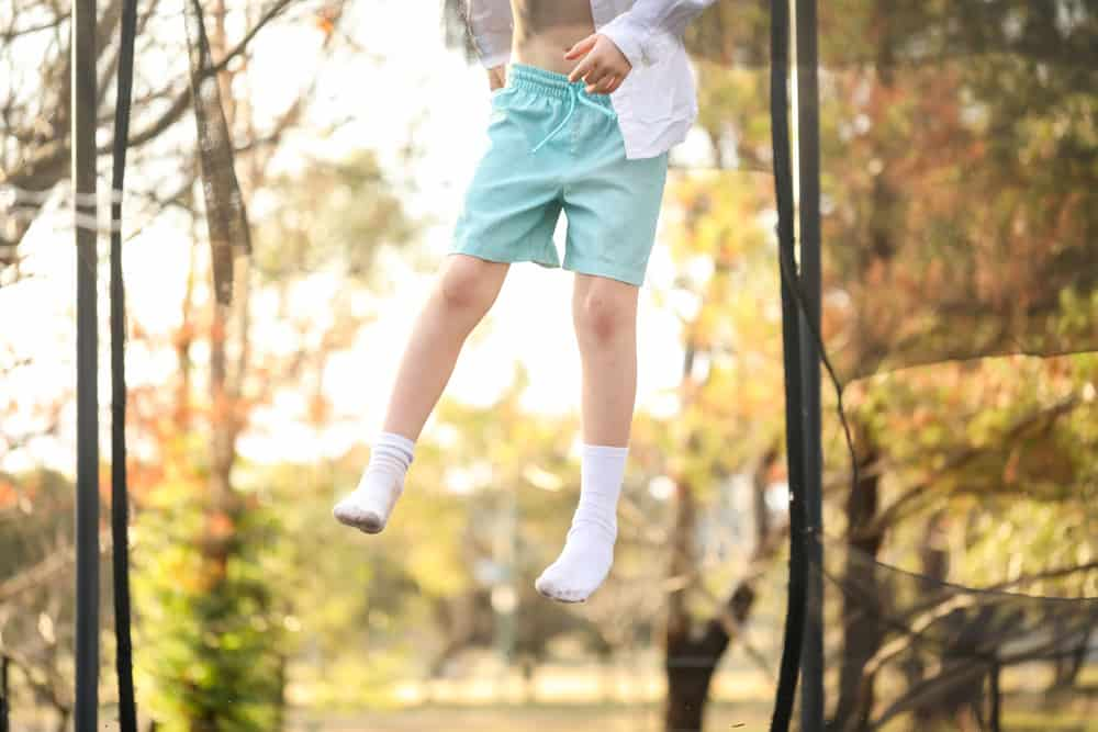 A boy jumping on the trampoline wearing a pair of blue shorts and socks.
