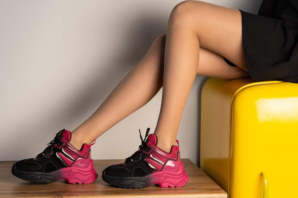 This is a close look at a woman wearing chunky ankle-high sneakers.