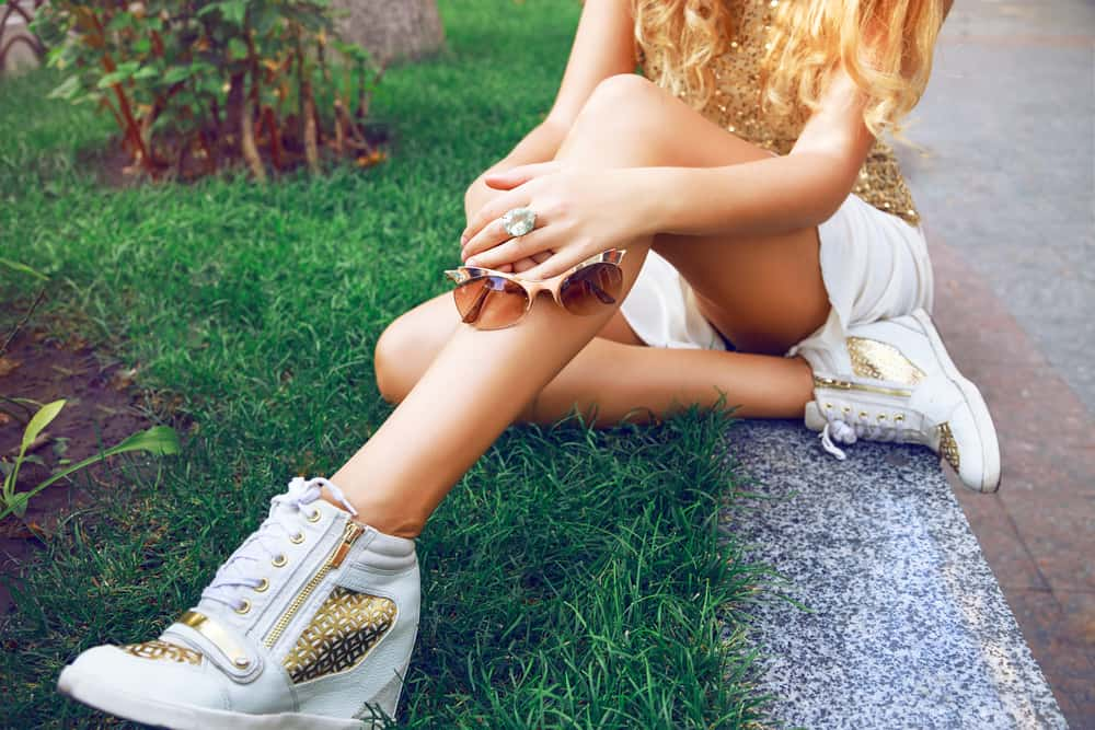 This is a close look at a stylish woman wearing short shorts and high sneakers.