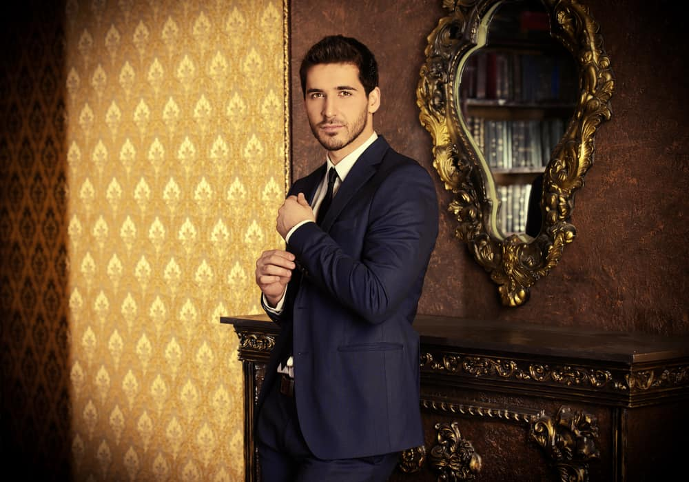 Man in formal coat standing inside a classic interior.