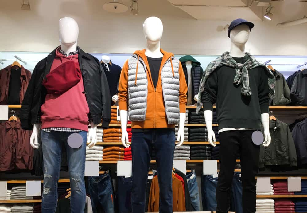 Men's clothing store with mannequins and shelves.