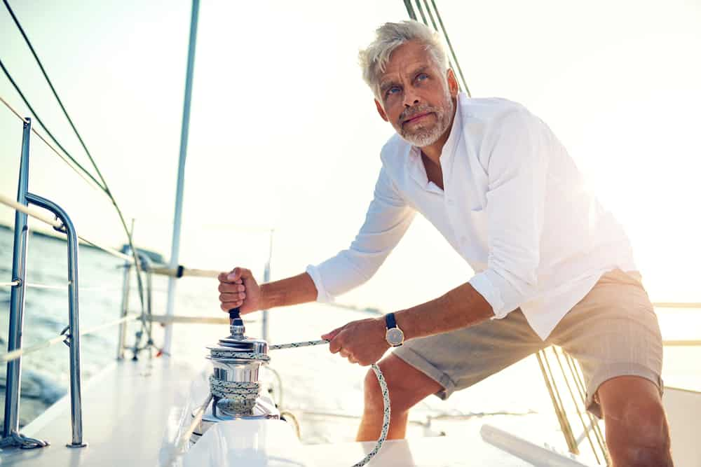Man in a white polo standing on the deck of his boat.