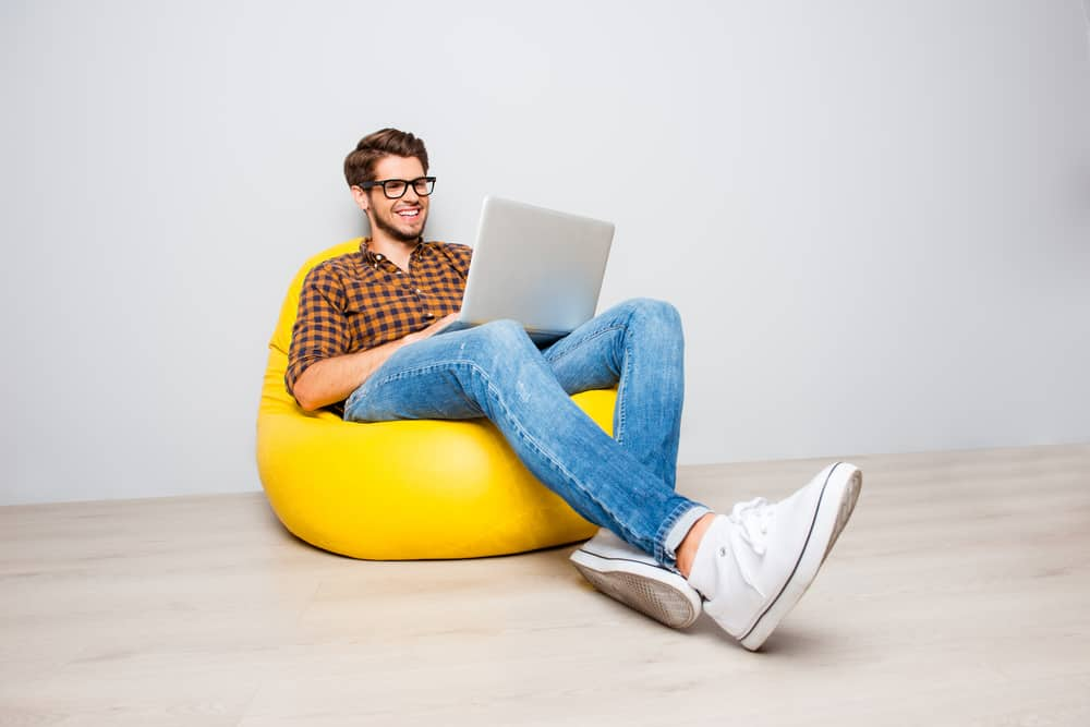 Man in checkered polo sitting on a yellow pouf while he uses his laptop.