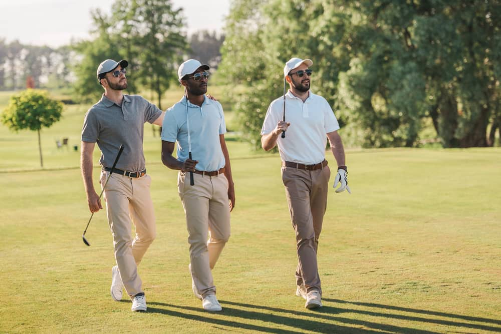 Men in caps and sunglasses holding golf clubs as they walk on the lawn.