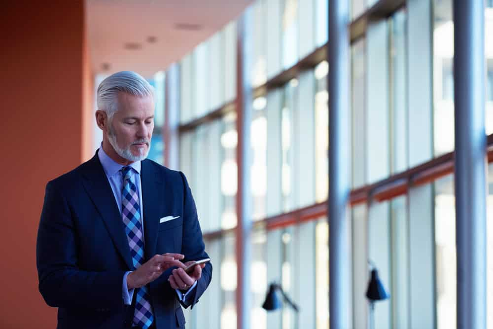 Senior businessman texting inside the office.