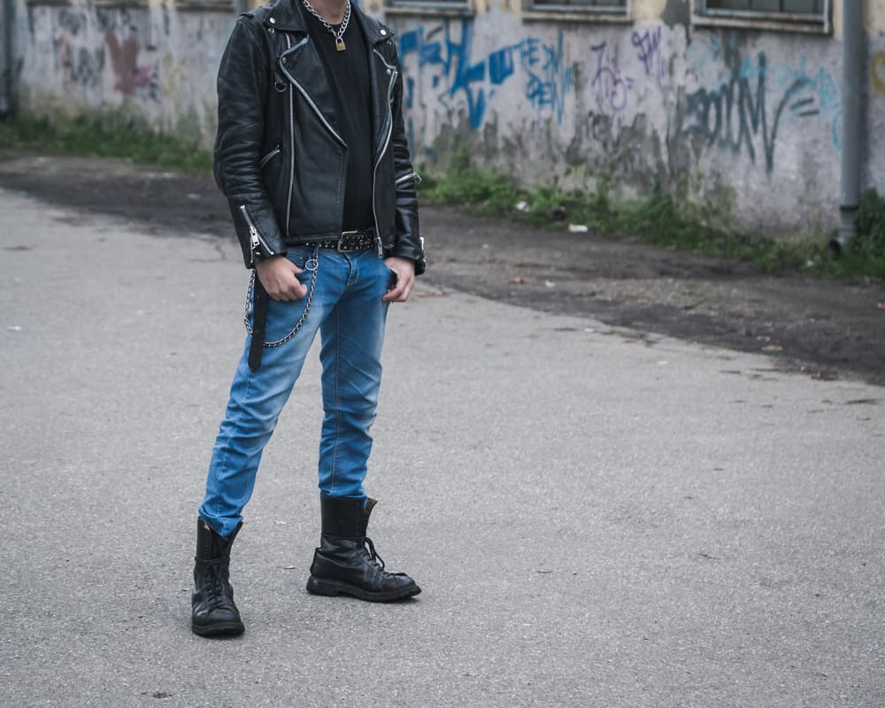 Punk guy wearing leather jacket, denim pants, and boots.