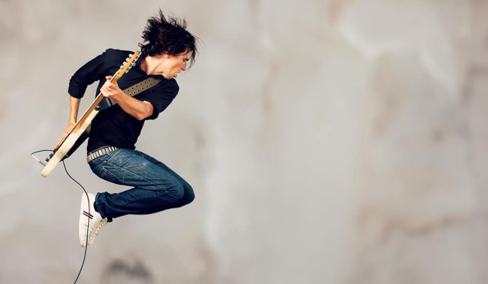 A rocker jumps while playing his guitar.