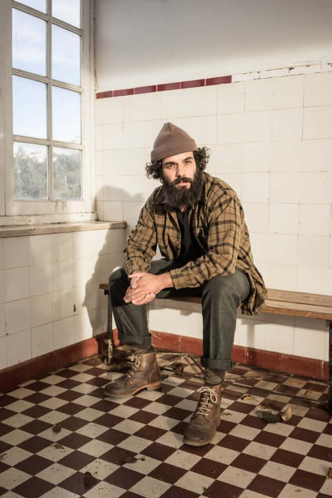 Bearded man in rugged polo and pants sitting on a bench.