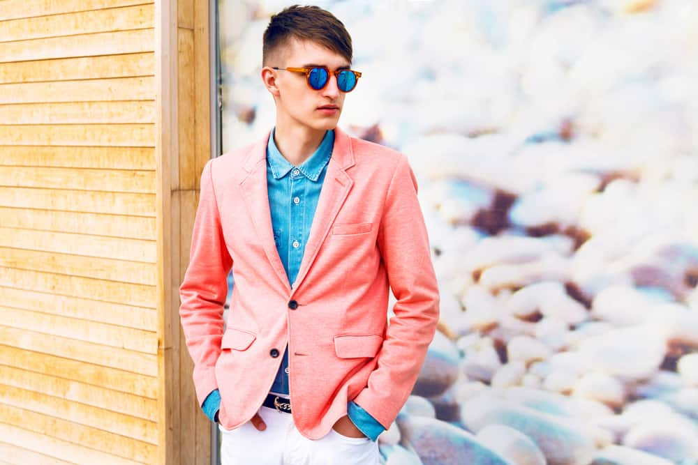 Portrait of a young man wearing shades and trendy bright clothes.