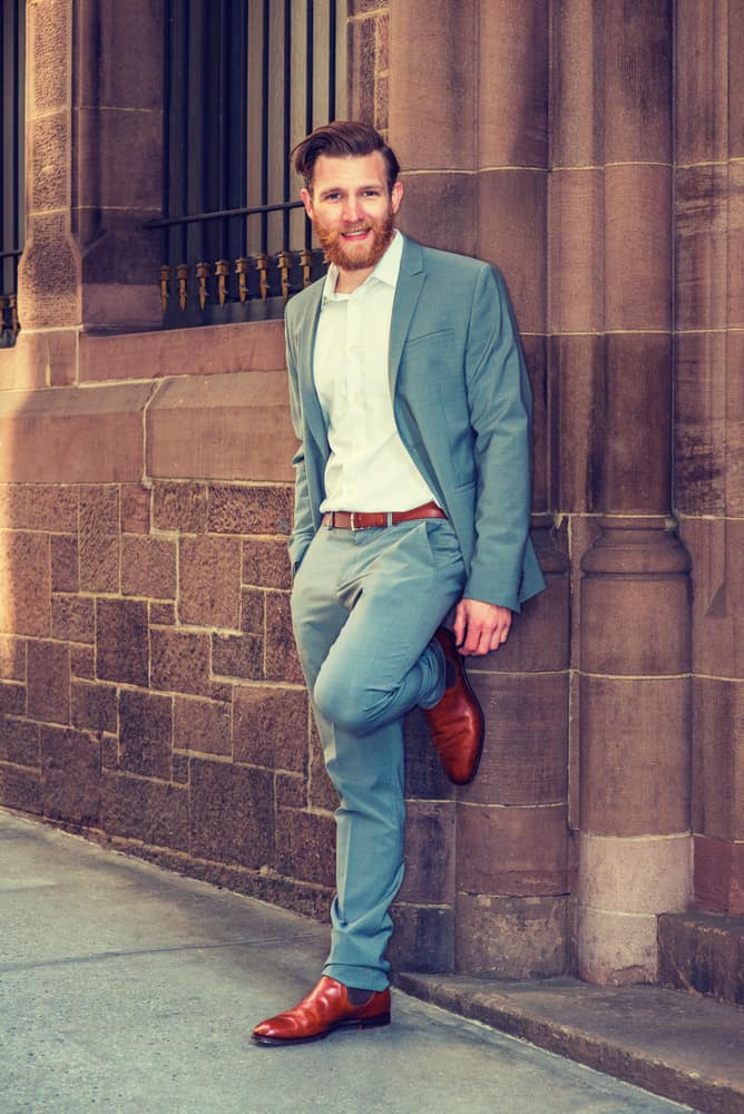 Man in a semi-formal clothes standing against vintage wall.