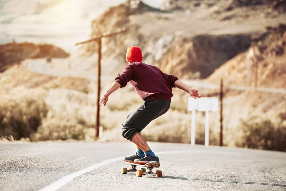 Skateboarder rides by mountain road.