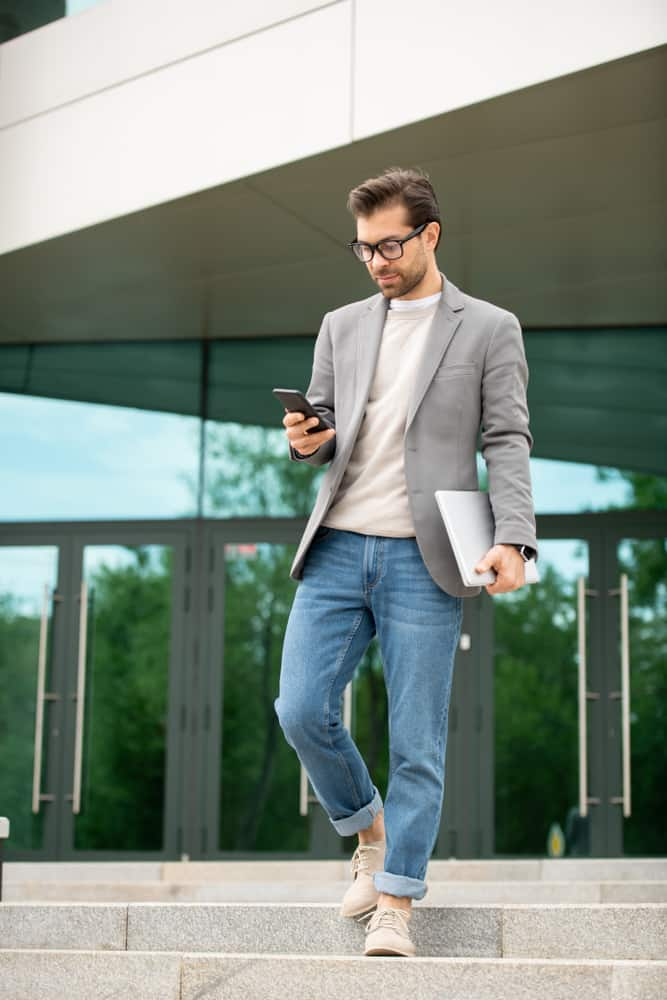 Man in a smart casual texting as he walks down the stairs.