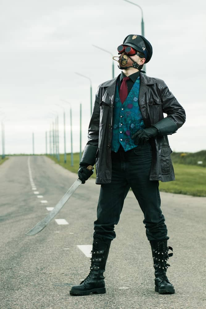 Man in steampunk style clothes poses on the road.