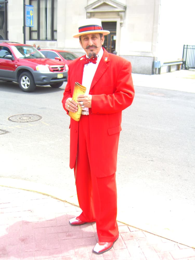 A man wearing a zoot suit with hat and leather shoes.