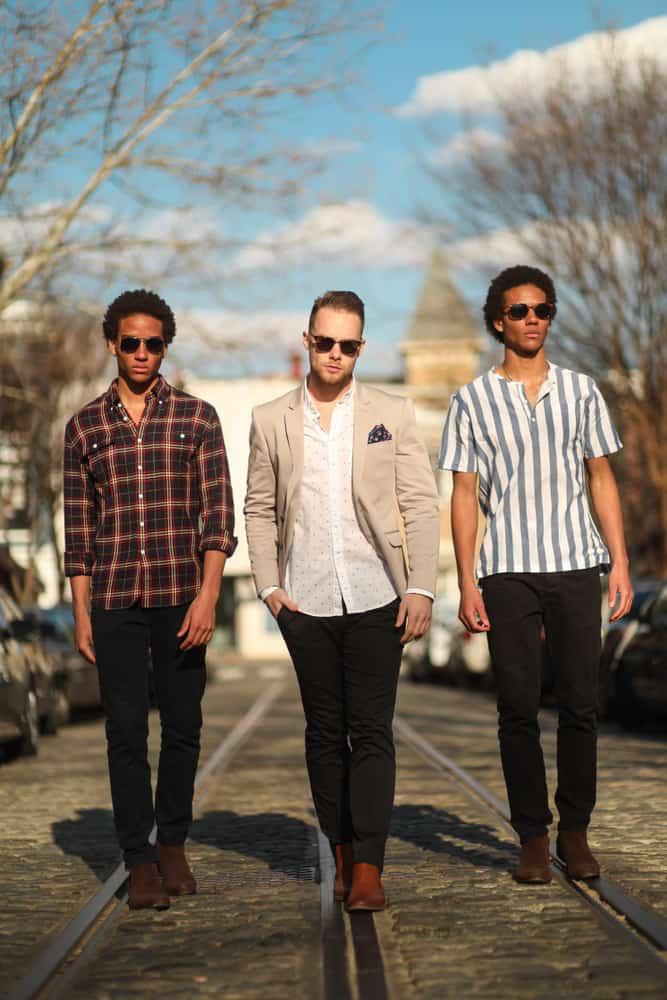 A group of men in streetwear walk down a cobblestone street.