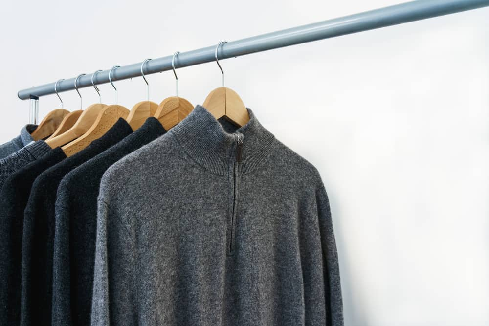 This is a close look at a rack of sweaters on display.