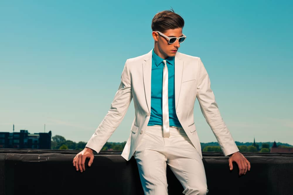 Man in vintage look wearing white suit and glasses.