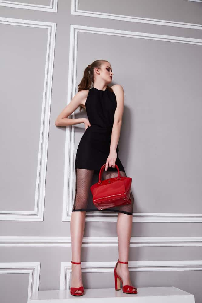 This woman accessorized her little black dress with red shoes, a red purse and red lips.