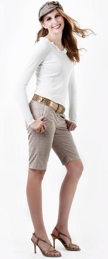 This is a close look at a woman wearing a pair of khaki Bermuda shorts.