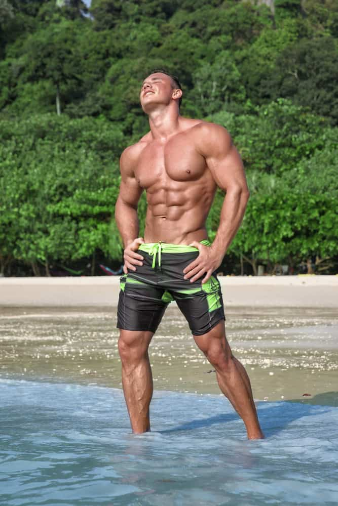 A man wearing a pair of swimming board shorts at the beach.