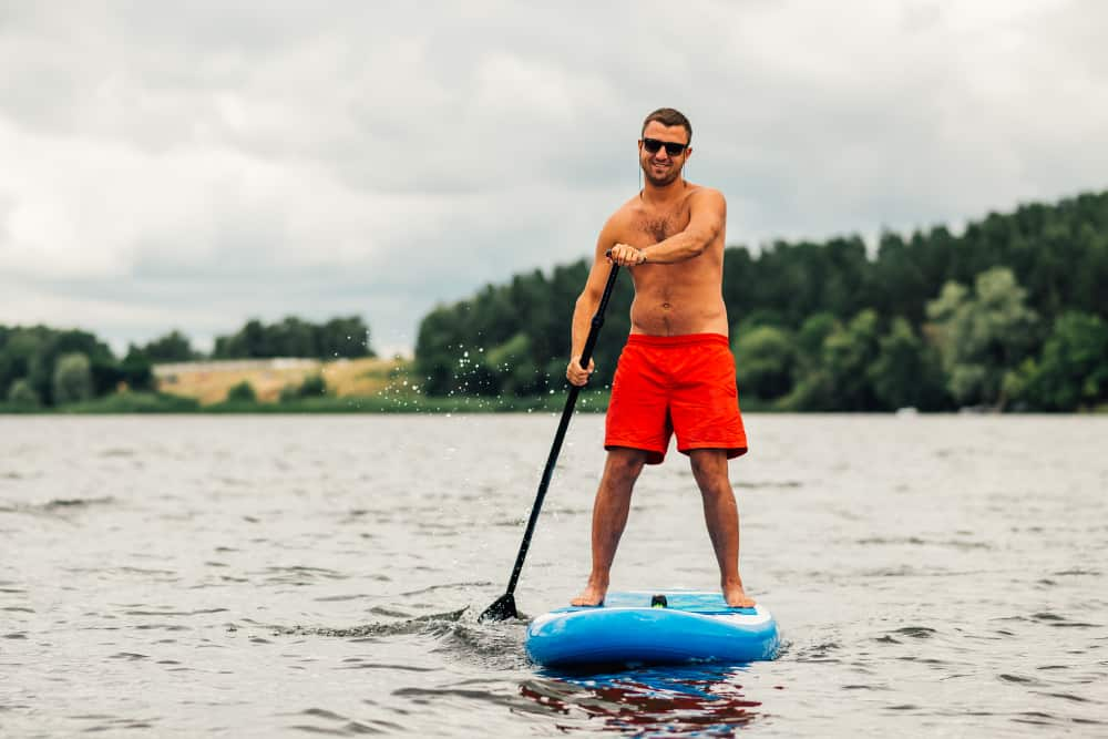 A man wearing a pair of red fitness board shorts while paddle boarding.