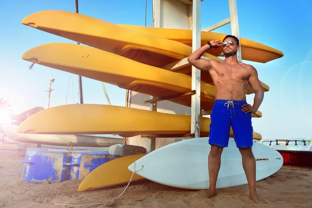 A man wearing a pair of blue lifeguard board shorts.