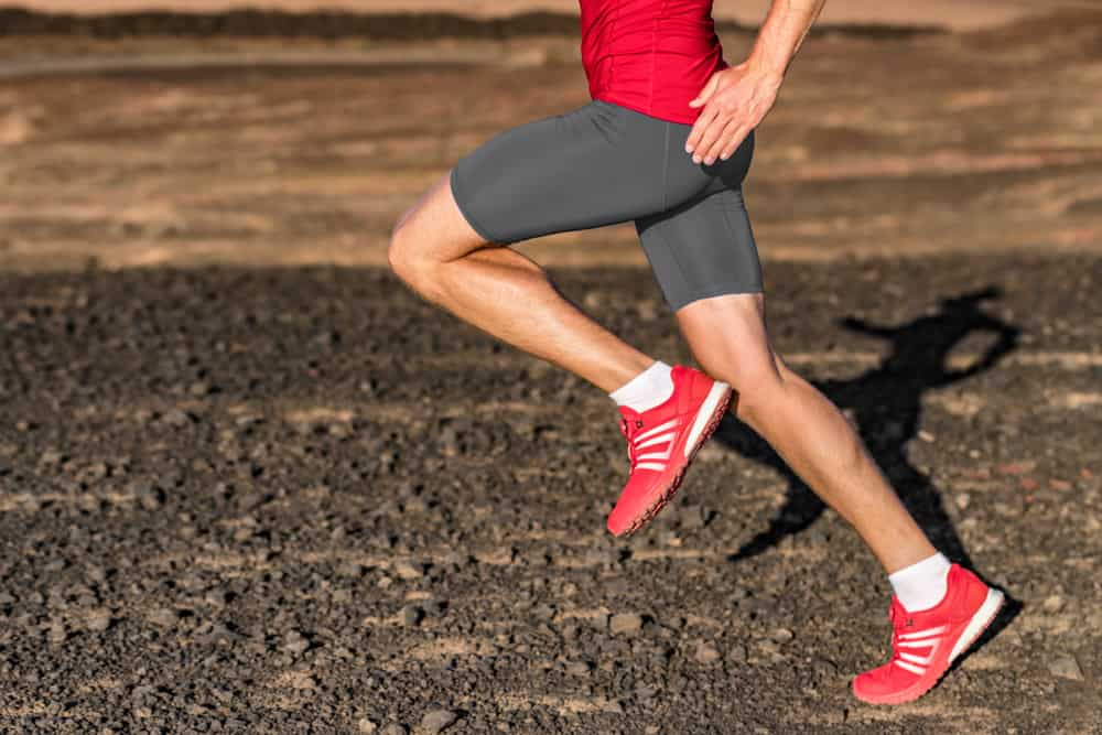 This is a close look at a man running on a rocky field while wearing a pair of compression shorts.