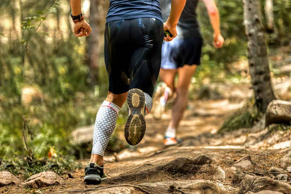 This is a close look at a man running on a forest trail wearing a pair of compression shorts.