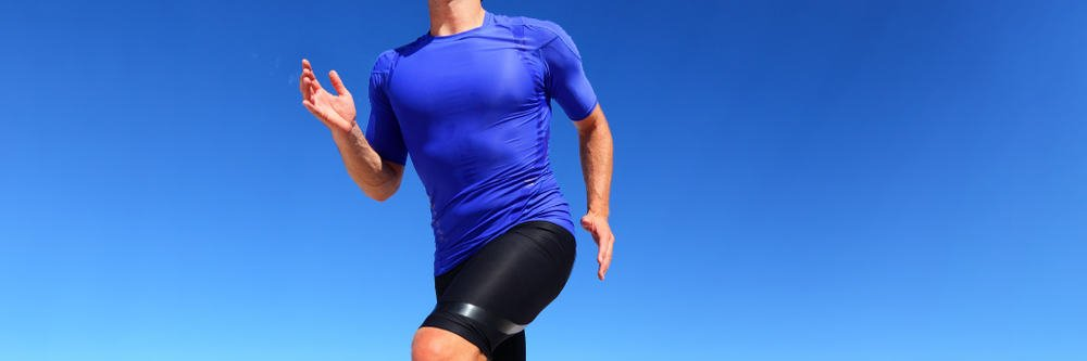 This is a close look at a man running wearing a pair of black compression shorts.