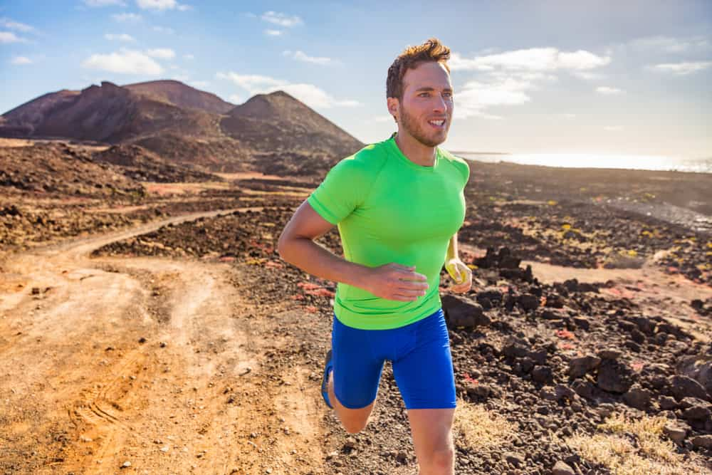 This is a close look at a man running on a mountain trail wearing a pair of compression shorts.