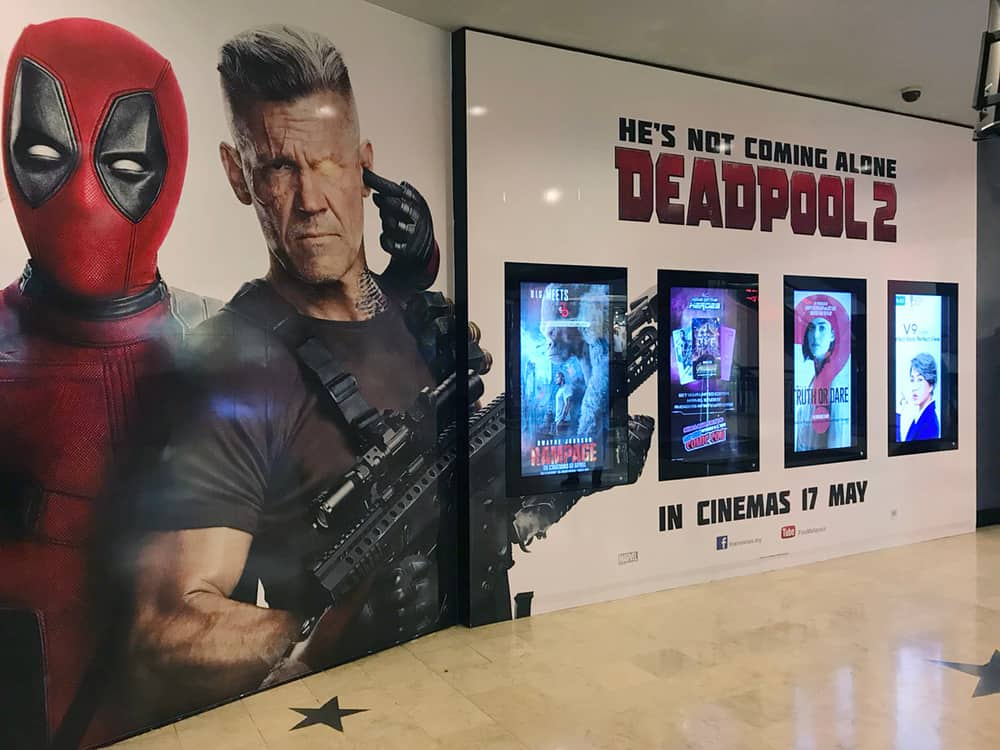This is a close look at a coming soon wall display at a theater featuring a Deadpool 2 poster.