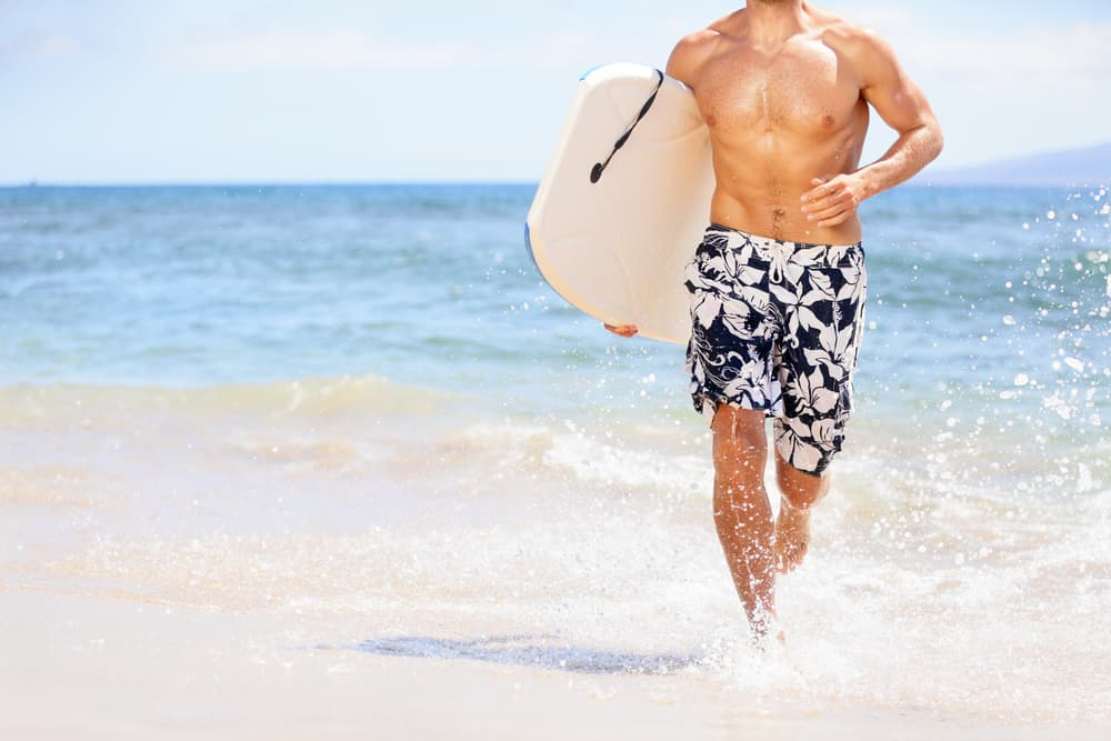 This is a close look at surfer wearing floral board shorts at the beach.