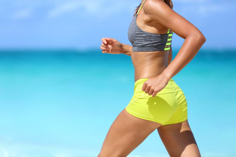 A woman jogging by the beach wearing midi shorts.